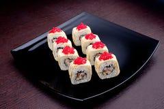 套寿司maki用在黑色的盘子的鱼子酱 在背景的日本食物 库存照片