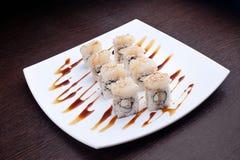 套寿司maki用蟹肉装饰用在白色板材的一个甜调味汁 在背景的日本食物 免版税库存照片