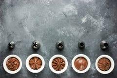 套巧克力奶油漩涡和金属喷管糖果店的 库存照片