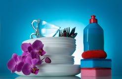 套干净的盘和兰花开花,洗涤剂,海绵,在蓝色 免版税库存图片
