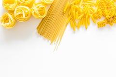 套意大利面食 未加工的意粉, fusilli, penne,在白色背景顶视图拷贝空间的意大利细面条 免版税库存照片