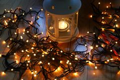 套有圣诞灯和棒棒糖的白色灯笼在木地板上 免版税库存图片