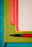 套有笔的笔记本在深蓝背景顶视图 免版税库存照片