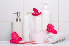 套有红色花的白色化妆瓶在铺磁砖的墙壁 免版税图库摄影