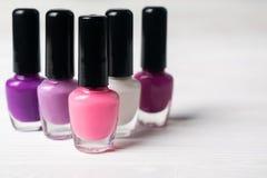 套桃红色和紫罗兰色五颜六色的指甲油瓶 图库摄影