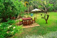套椅子和桌在花卉庭院中 免版税库存照片