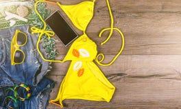 套海滩给黄色比基尼泳装,镯子,牛仔裤短裤,在黑暗的木背景的玻璃穿衣 顶视图 使布赖顿椅子日甲板英国节假日懒人海边有风夏天的星期日靠岸 库存图片