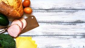 套烹调的产品-新鲜面包,鸡蛋,切了火腿、硬花甘蓝、乳酪、鲕梨和砍肉刀在白色葡萄酒木su 库存图片