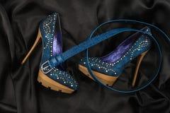 套牛仔裤鞋子和一条蓝色传送带在商店窗口里 图库摄影