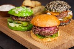 套特写镜头三微型自创汉堡用大理石牛肉和菜在一个木板 图库摄影