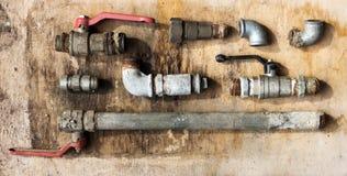 套老水力水管和管道在一个老木板 免版税库存图片