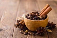 套被仔细考虑的酒的香料在木桌上的陶瓷碗 图库摄影