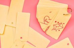 套被回收的标签标记栓与金属圆环对与逗人喜爱的桃红色图画的一个笔记薄在桃红色背景 免版税库存图片