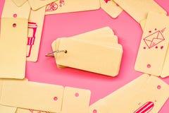 套被回收的标签标记栓与金属在桃红色背景的圆环对与逗人喜爱的桃红色图画和桃红色划线员的一个笔记薄或者笔 免版税库存照片