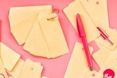 套被回收的标签标记栓与金属在桃红色背景的圆环对与逗人喜爱的桃红色图画和桃红色划线员的一个笔记薄或者笔 库存图片