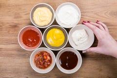 套调味汁-番茄酱、蛋黄酱、芥末酱油、bbq调味汁、芥末五谷和石榴在木桌上调味 库存照片