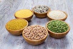 套谷物,豌豆,米,小米,在木背景的竹碗洒的鸡豆 免版税库存照片