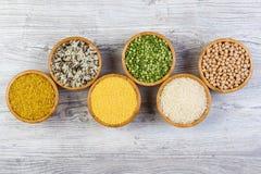 套谷物,豌豆,米,小米,在木背景的竹碗洒的鸡豆 库存图片