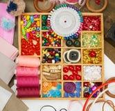 套辅助部件和首饰对刺绣,缝合的辅助部件顶视图,裁缝工作场所,许多为针线, embro反对 免版税图库摄影