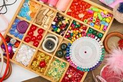 套辅助部件和首饰对刺绣,缝合的辅助部件顶视图,裁缝工作场所,许多为针线, embro反对 库存图片