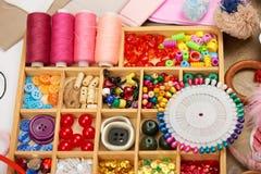 套辅助部件和首饰对刺绣,缝合的辅助部件顶视图,裁缝工作场所,许多为针线, embro反对 免版税库存图片