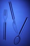 透明叉子、匙子和在蓝色背景的一把刀子 免版税库存照片