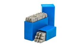 套金属邮票在白色背景隔绝的蓝色塑料盒的字母表和数字拳打 免版税库存照片