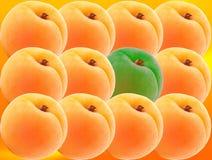 套黄色桃子和一个绿色桃子 免版税库存图片