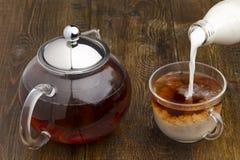 套玻璃茶壶、茶杯和瓶牛奶 库存图片