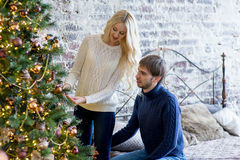 套头衫的装饰圣诞树的恋人愉快的夫妇  免版税库存图片