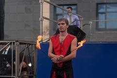 奥伦堡,俄罗斯- 25 07 2014年:玩杂耍的灼烧的火炬 免版税库存图片