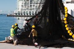 奥克兰,新西兰- 2012年6月14日:小组维护工业渔网的口岸工作者由卷扬机ovn口岸背景提起了 图库摄影