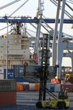 奥克兰,新西兰- 4月17日:轮式起重机和拿着容器的载体卡车在海港 库存照片