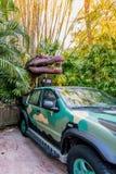 奥兰多,佛罗里达,美国- 2017年12月:在灌木之间的恐龙与他的嘴开放陈列他的在一辆汽车的牙在主题乐园 库存图片