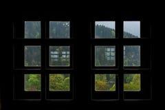 奥地利森林看法在提洛尔通过现出轮廓的小方形的Windows 库存图片