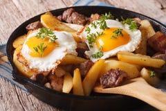 奥地利食物:油煎的土豆用肉和鸡蛋在平底锅closeu 库存图片