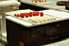 奥地利,维也纳- 2011年5月:准备的维也纳甜点咖啡馆德梅尔在市中心,车间,手工制造白色和红色糖果 库存图片