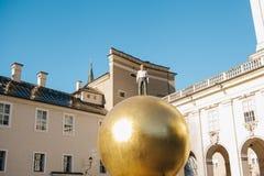 奥地利,萨尔茨堡- 01 01 2017年 金黄球雕象看法与人的在城市广场安置的上面的正式成套装备的  库存照片