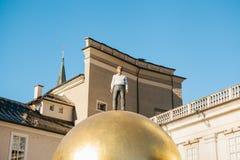 奥地利,萨尔茨堡- 01 01 2017年 金黄球雕象看法与人的在城市广场安置的上面的正式成套装备的  免版税库存照片