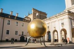 奥地利,萨尔茨堡- 01 01 2017年 金黄球雕象看法与人的在城市广场安置的上面的正式成套装备的  免版税库存图片