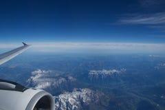 奥地利-2016年10月:阿尔卑斯如被看见从一架飞机、翼视图与平面涡轮或引擎 免版税库存照片