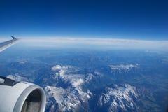奥地利-2016年10月:阿尔卑斯如被看见从一架飞机、翼视图与平面涡轮或引擎 库存图片