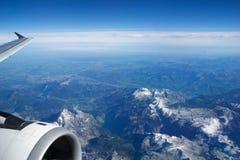 奥地利-2016年10月:阿尔卑斯如被看见从一架飞机、翼视图与平面涡轮或引擎 免版税图库摄影