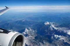 奥地利-2016年10月:阿尔卑斯如被看见从一架飞机、翼视图与平面涡轮或引擎 免版税库存图片