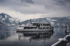 奥地利-滨湖采尔- 16 12 2017个游人巡航在有雪的冻湖和在背景的美丽的山 Touris 库存图片