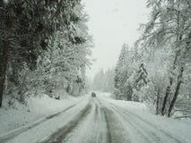 奥地利 驾驶射击,观点的司机 驾驶在路在期间降雪的英尺长度 免版税库存图片