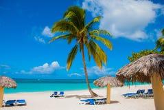 奥尔金,古巴, Playa埃斯梅拉达 美好的加勒比海土耳其玉色颜色和棕榈树在海滩 太阳懒人和umbrell 图库摄影