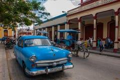 奥尔金,古巴:在街道上的减速火箭的蓝色老汽车和马推车 图库摄影