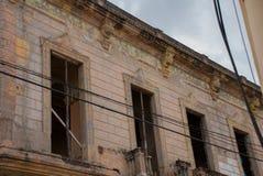 奥尔金,古巴:没有玻璃的被破坏的老房子在街道上 库存图片