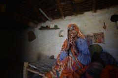 奥拉奇哈,印度, 2017年11月28日:坐在她的床上的老妇人 库存照片